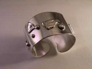 Armring i silver dekorerad med silverdetaljer och en kula i guld Såld